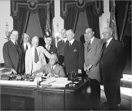 FDR signs the Glass-Steagall Banking Act into law in 1933 while pro-segregationist Democrats Carter Glass (with his hand on Roosevelt's shoulder) and Henry Steagall (at FDR's left), look on.