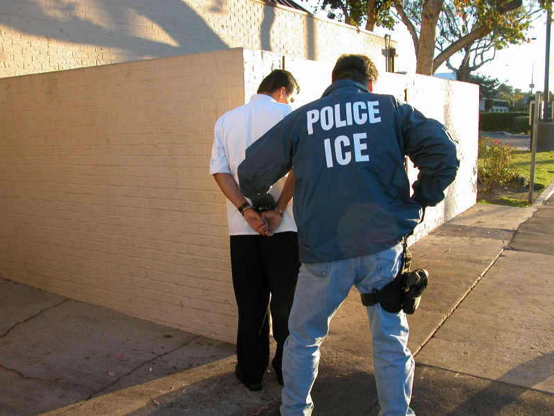 ICE officer arresting a suspected illegal immigrant